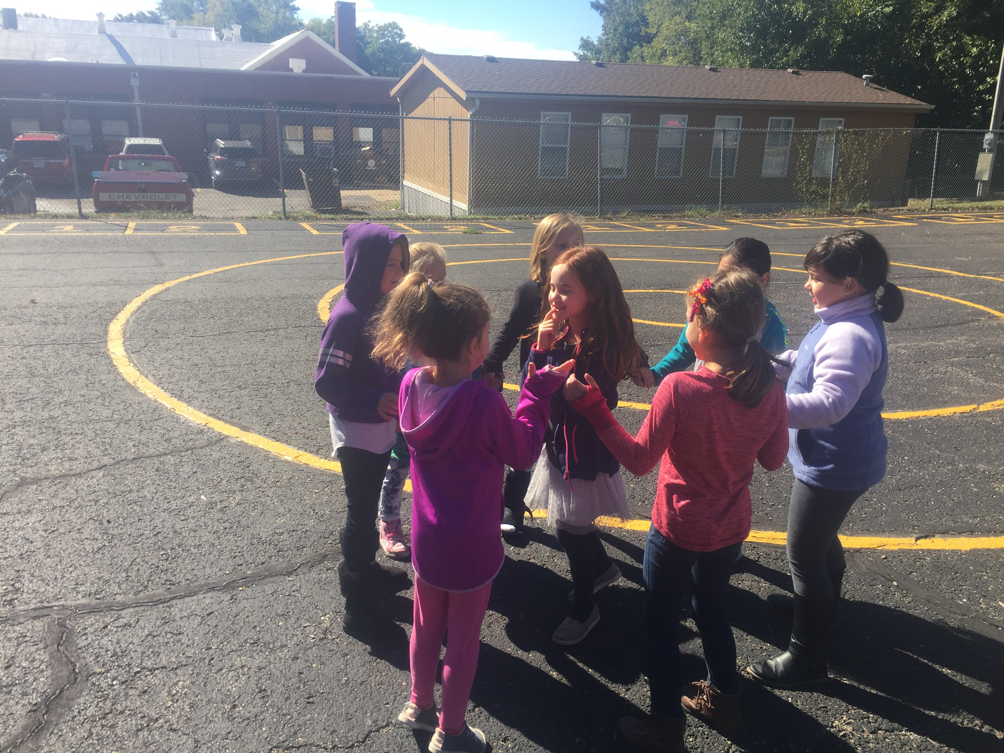These 1st grade girls are enjoying a fun game of Little Sally Walker on this beautiful fall day!